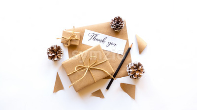 Gift boxes, fir cones, note with a message and a pencil. White background. Holiday concept. Top view Stock Photo