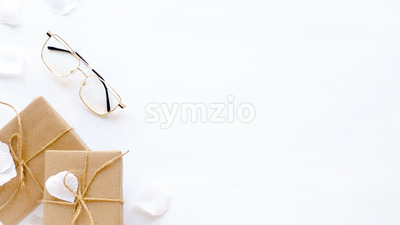 Gift boxes, glasses, rose petals. White background. Holiday concept. Top view Stock Photo