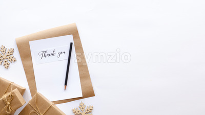 Gift boxes, decoration, notebook with a message and a pencil. White background. Holiday concept. Top view Stock Photo