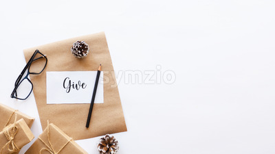 Gift boxes, fir cones, note with a message and a pencil, glasses. White background. Holiday concept. Top view Stock Photo