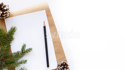 Notebook with a pencil, fir cones, Christmas tree branch. White background. Holiday concept. Top view Stock Photo