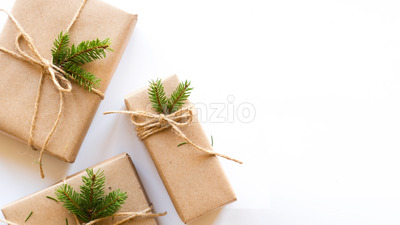 Gift boxes with attached Christmas tree branch. White background. Holiday concept. Top view Stock Photo