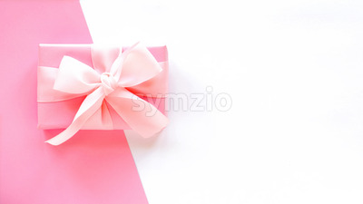 A gift box with a tape on two-color background. Pink and white colors. Holiday concept. Top view Stock Photo