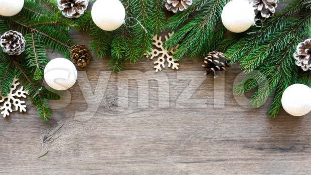 Christmas tree branches with firs cones and holiday decorations. Wooden background. Holiday concept. Top view Stock Photo