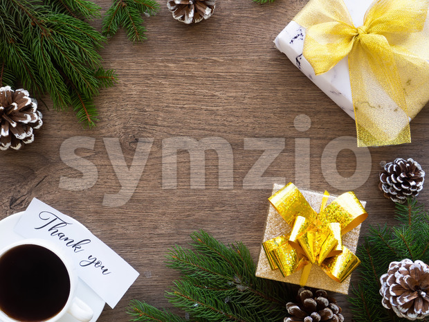 Christmas tree branches with firs cones and gift box with cup of coffee, note with a message. Wooden background. Holiday concept. Top view Stock Photo