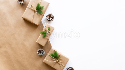 Gift boxes with Christmas tree branches and fir cones on two-color background. Pink and white colors. Holiday concept. Top view Stock Photo