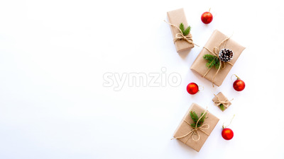 Gift boxes with Christmas tree branches and fir cones on white background. Holiday concept. Top view Stock Photo