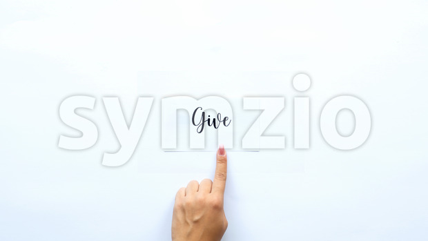 Female finger showing on a note with a word Give on it. White background Stock Photo
