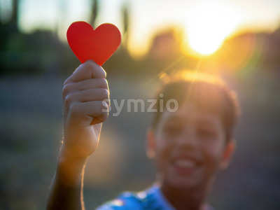 Smiling boy holding a red heart, setting sun. Love concept Stock Photo