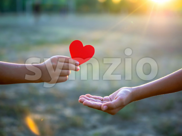 A kid is giving a man a red heart, setting sun. Love concept Stock Photo