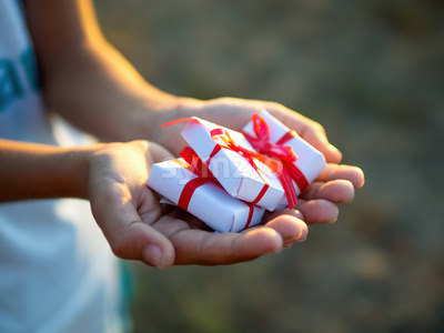 Male hands holding a few white gift boxes with red tapes. Holiday concept Stock Photo