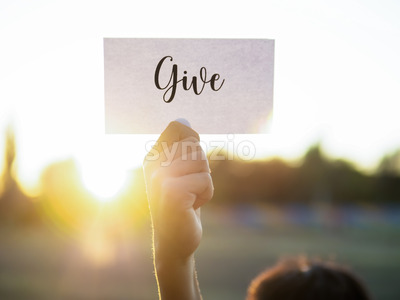 Male hand holding a note with word Give on it, setting sun Stock Photo