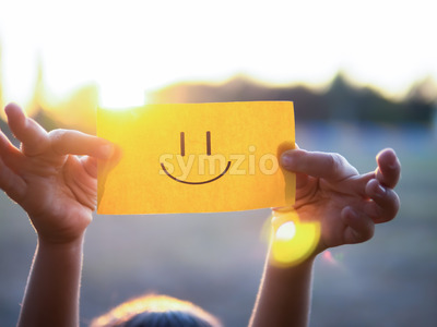 A kid is holding a paper with positive face on it, setting sun Stock Photo