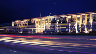 Government building and street with cars in the evening in Chisinau, Moldova Stock Photo