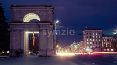 Arch and street with cars in the evening in Chisinau, Moldova Stock Photo