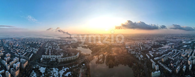 Panorama of Bucharest from a drone, districts of residential buildings with park and lakes, fog other the ground, Romania Stock Photo