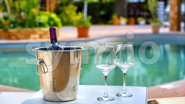 Red wine bottle and glasses by the hotel pool Stock Photo