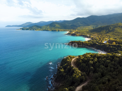 Aerial drone view of blue sea and windy mountain roads in Halkidiki, Greece Stock Photo