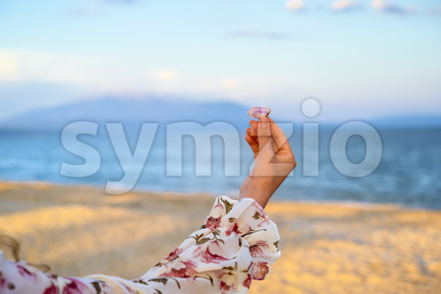Woman in pink flower dress holding a sea shell over sea and mountains background at the beach in Greece Stock Photo