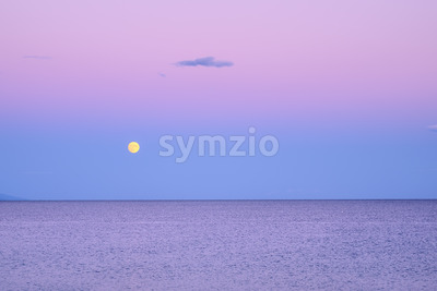 Dark purple sky with yellow moon over sea after sunset in Greece Stock Photo