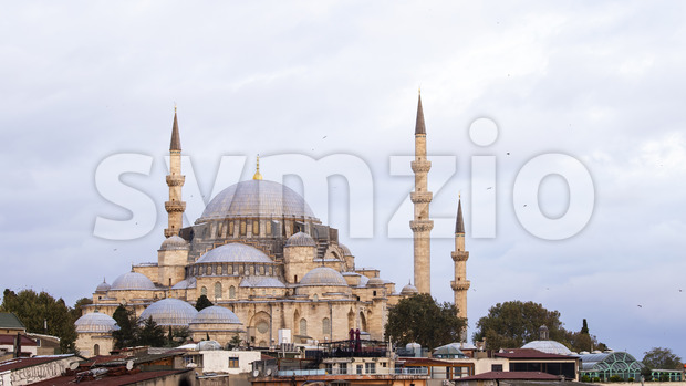 Rustem Pasha Mosque with towers at cloudy weather, roofs of the buildings on the foreground in Istanbul, Turkey Stock Photo