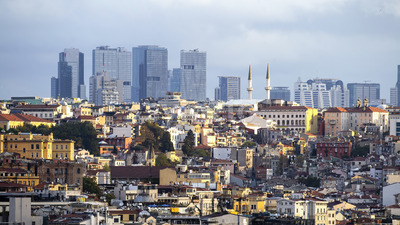 A lot of low residential and high modern buildings in the distance, sunlight and cloudy sky in Istanbul, Turkey Stock Photo