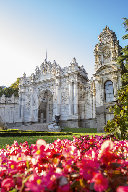 Facade of the Dolmabahce Palace with gardens full of greenery and flowers in front of it in Istanbul, Turkey Stock Photo