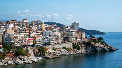 Multiple buildings located on the Aegean sea cost, road passing over the rocky coastline, green hill on the background in Kavala, Greece Stock Photo