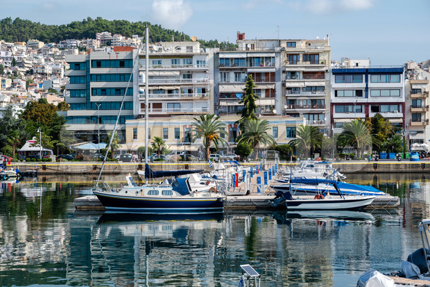 Port with lots of moored boats, buildings on the Aegean sea cost of Kavala, green hill on the background, Greece Stock Photo