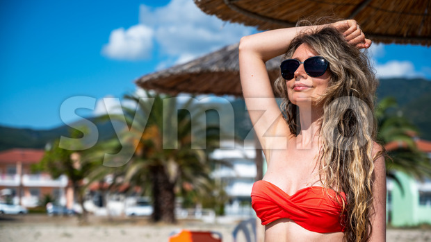 Portrait of a caucasian woman in sunglasses and red swimsuit with raised hand under a umbrella on the beach in Riviera, Greece Stock Photo