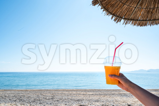 Woman's hand holding a cup with a drink under a umbrella with beach and Aegean sea on the background, Asprovalta, Greece Stock Photo
