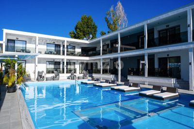 Inner court of Avaton Luxury Resort with a pool, sunbeds and multiple hotel room's entrances in Asprovalta, Greece Stock Photo
