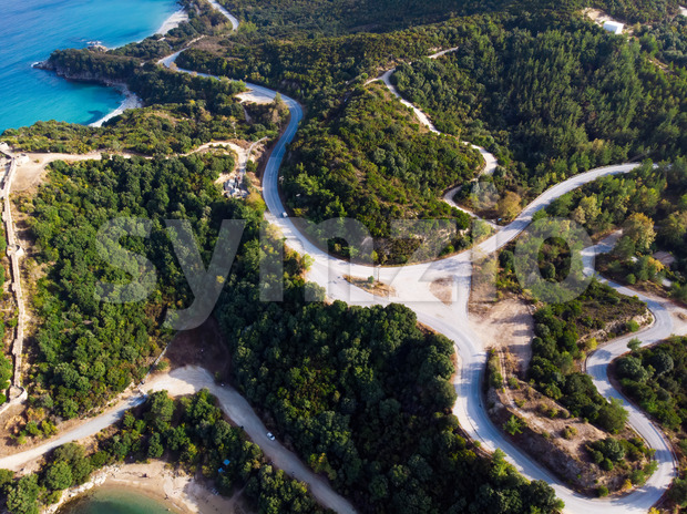 Aegean sea cost of Greece, twisting road, hills covered with lush greenery, view from the drone, Greece