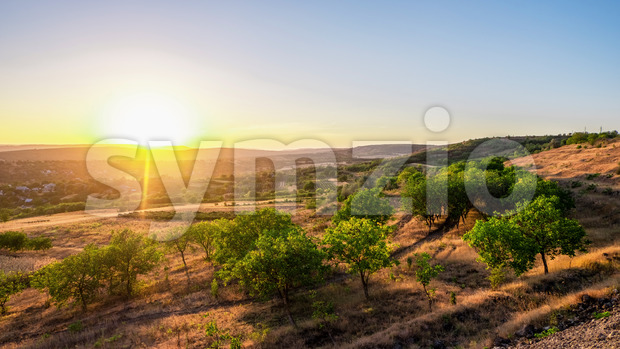 Sunset in Moldova, view from the hill slope with green trees, village in the valley Stock Photo