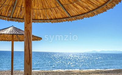 Reed umbrellas and sun beds at the empty beach in Asprovalta, Greece Stock Photo