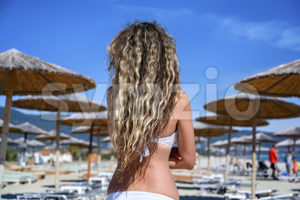 Happy young woman resting at the beach in Asprovalta with reed umbrellas and sunbeds, Greece Stock Photo