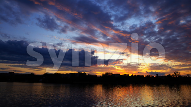 Sunset in Moldova, lush clouds with yellow light reflected in surface of the water on the foreground