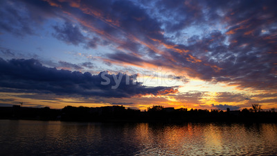Sunset in Moldova, lush clouds with yellow light reflected in surface of the water on the foreground Stock Photo