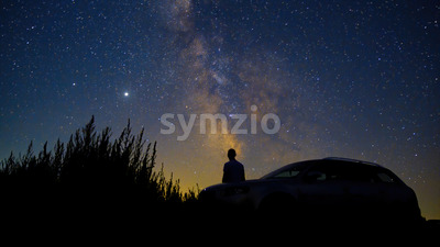 Man with his car looking at sky full of shining stars, long exposure, Moldova Stock Photo