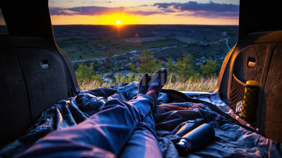 A man lying in the opened trunk of the car with view on the nature of Moldova, fields, hills at sunset Stock Photo