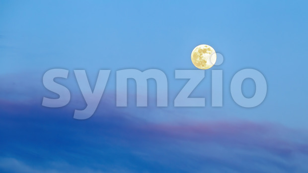 Huge yellow moon in the sky consisting of shades of blue and violet Stock Photo