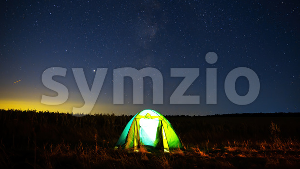 A tent in a field with light inside and sky full of shining stars in the background, Moldova Stock Photo