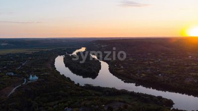 Sunrise in Moldova, village with orthodox church, river dividing into two parts, hills and fields on the background, view from the drone Stock Photo