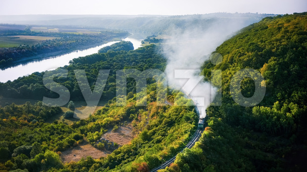Moving train on railway with high column of smoke, flowing river, hills and railway on the foreground, fields on the other shore in Moldova Stock Photo