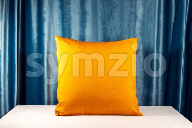 Horizontal shot of an orange pillow on the desk. Blue velvet background. Light casting soft shadows on the table. Interior design idea Stock Photo