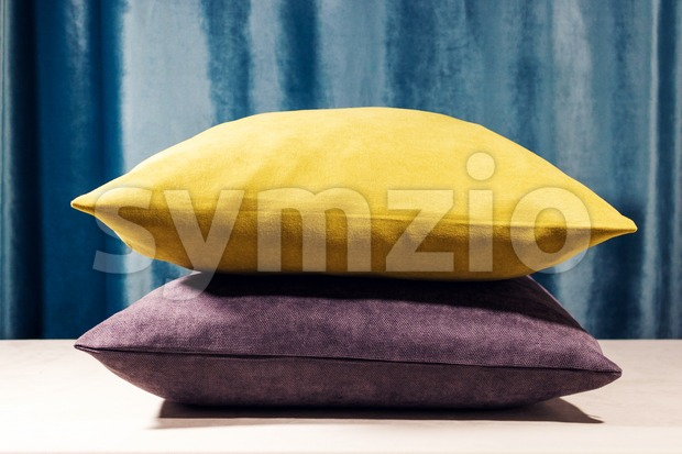 Yellow and purple pillows standing one on to another. Blue velvet background. Soft light coming from the top, Warm whitebalance Stock Photo