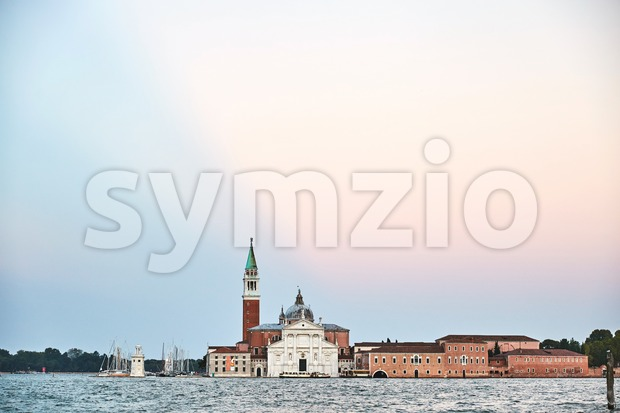 Venice city with famous cathedral Santa Maria della Salute on water and bell tower at sunset. Italy beauties