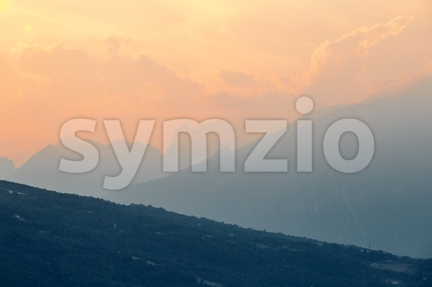 Mountains at sunset near Santa Croce Lake. Cloudy sky. Province of Belluno, Italy Stock Photo