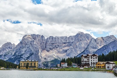 Lake Misurina with city and mountains on background. Blue sky in clouds. Province of Belluno, Italy Stock Photo