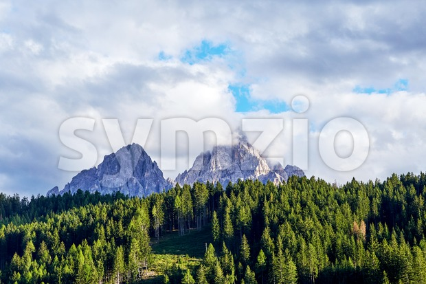 Dolomites mountains in warm season. Green forest on foreground. Italy beauties